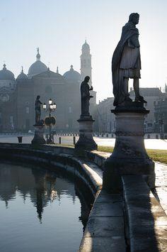 Prato della Valle. Padua, Italia. Prato della Valle (conocido localmente como Il Prato) es sin duda la plaza más característica de la ciudad de Padua. Con sus 90,000 metros cuadrados, se le considera la segunda más grande de Europa. Tiene una forma elíptica. En su centro, hay un enorme jardín rodeado por un canal artificial. Alrededor podemos encontrar 78 estatuas de los ciudadanos más notables en la historia de Padua.