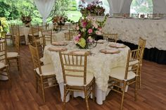 """Fairy Tale Tents & Events - Frankfort, IL - 40'x40' High-Peak Fairy Tale Frame Tent with white full gathered tent liner, cathedral window side walls, white side pole swags with white ties, and full tent flooring; 60"""" round tables with ivory polyester table linens, ivory Antoinette overylays, ivory polyester napkins, gold charger plates and gold chiavari chairs and ivory chair pads; 12 person head table on risers with ivory lamour satin gathered skirting with brooches"""