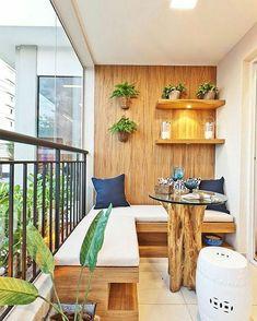 Varanda com banco fixo e mesa de centro e parede de madeira.