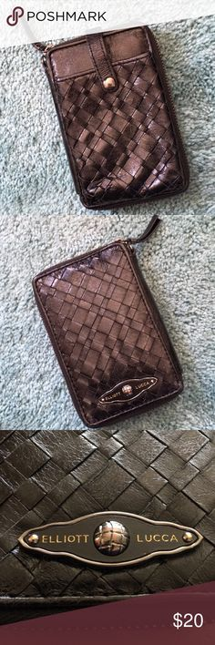 Elliot Lucca black leather wallet This wallet did have a wristlet band to go with it but somehow in packing and unpacking I lost it.  The front is a basket weave leather with a snap front pocket I found to be excellent for carrying business cards. Or you could also carry other personals in there of your choice. It is 100% leather.  Elliott Lucca products last a long time. Elliot Lucca Bags Wallets