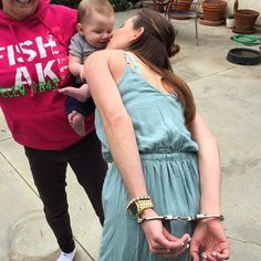 Woman handcuffed behind back kisses neighbor's toddler.