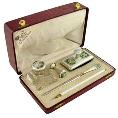 The set consists of a hinged cut crystal inkwell decorated with beveled edges and a beautiful wheel cut starburst at the base; A wax seal with blank matrix; blotter; dip pen and letter opener. Each with guilloche enamel featuring a yellow rose with lush green leaves on a pale blue background, trimmed with a lighter shade of blue enamel. The dip pen having an allover pale blue guilloche enamel, the pen nib ma