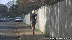 Sexy woman in black sheer 10 denier pantyhose and very short mini skirt in the street.