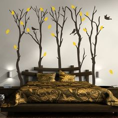 5 autumn tree wall decals in matte black with orange leaves sparsely placed and 3 flying vinyl birds. This wall mural is placed on a beige wall behind a bed.