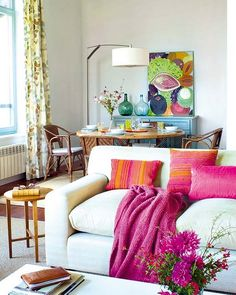 love the white couch with hues of bright magentas and oranges, the gold side table, and the vases on the back table as decoration