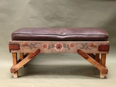 Classic Monterey bench with unusual floral decoration on faded green background with faded yellow legs.