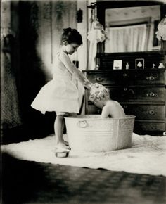 The Saturday Bath. Young girl giving boy a shampoo in a washtub. (1909) Missouri History Museum