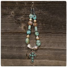 A turquoise and sterling cross hanging from rough pearls, turquoise, shell, druzy beads and a custom sterling clasp! By: Remagine Designs.  Available at: http://www.shopthescarab.com/collections/desertrosecollection/products/turquoise-cross-necklace