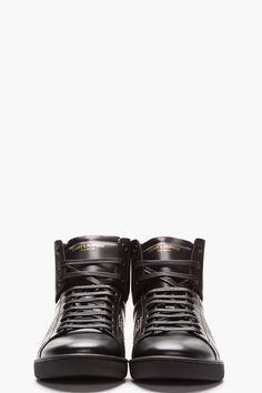 SAINT LAURENT - Black Classic Studded Leather High-Top Sneakers High-top leather sneakers in black. Round toe. Black lace up closure with black eyelets. Logo print at tongue in gold. Padded tongue and collar. Mini stud embellishments at sides. Paneled upper. Tonal rubber foxing. Tonal stitching. Leather upper, rubber sole. Made in Italy. $700 CAD