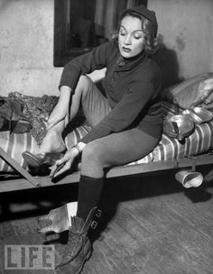 """""""During her tour of the European front, Dietrich eats, sleeps, and dresses like the G.I.s, but at showtime, as in this February 1945 photo, she changes into a sequined gown and gold pumps."""""""