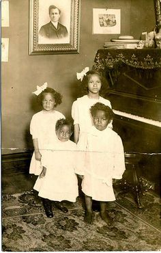 Four African American children, probably three girls and one boy, pose in a living room next to a piano in white dresses. c1910