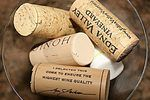 Creating a bulletin board from wine corks requires only a frame or backing, a hot glue gun, scissors, and corks.