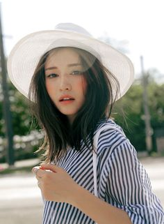 Street beauty with a sense of accessories: white summer hat matching hand bag. Blue striped blouse. #MoxyStyle #MoxyLady #MoxyBeauty