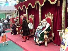 The Three Wise Men receiving children at a shopping centre in Spain. Letters with gift requests are left in the letterbox on the left-hand side.