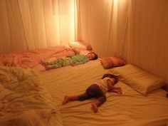 """Two mattresses put together on the floor with sheets on the walls to create a literal """"bed room""""."""
