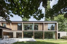 Exterior, Flat RoofLine, House Building Type, Wood Siding Material, Glass Siding Material, and Brick Siding Material The ground floor follows an L-shaped plan and is accessed from the garden via a concrete terrace.