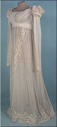 Circa 1805-1810 Embroidered Empire Muslin Gown. Excellent quality embroidery in neoclassical motif. The gown is a white muslin, only lined in the bodice, and the rest of the gown is fairly sheer. Modified square neckline. Gathered bust. Tiny pouf sleeve caps over long straight arms.