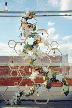 the geometric alter This honeycomb-inspired backdrop, interspersed with hanging bulbs and a stunning floral arrangement, is the ultimate backdrop for the urban wedding.