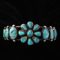 Braclet   Designer ? (Navajo) Hand pulled ingot round wire with old natural American turquoise stones set in plain silver bezels with applied silver drop beads framing the setting and capped end terminals. Circa 1920's-30's.