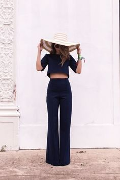 Love this outfit! Super chic but still sleek and classic. Flared trousers with a crop top and a big floppy hat, perfect.