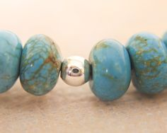 A close up view of a single sterling silver, round bead in between four turquoise stones. - check out our Treasure Hunt game - http://www.earthwhorls.com/product/gemstone-handmade-jewelry-sterling-silver-turquoise-necklace-1391sn/