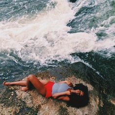 Image: @asiyami_gold Shown: A beautiful black girl with curly hair laying on a boulder beside the ocean.