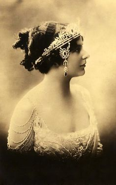 Fawn Velveteen - An incredibly intricate belle epoque tiara circa 1905. This piece has elements of the Greek Key motif, intertwined with small laurels in diamonds, and three large wreath motifs, each with a central oval stone. More laurels with similar smaller wreaths are suspended from a base line of diamonds just in front of each ear.