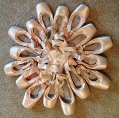 pointe shoe art | Wall art made from old pointe shoes.. Hot glue them onto a wire wreath ...