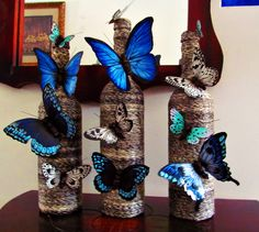 three wine bottles wrapped in twine and decorated with blue butterflies made of paper