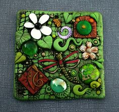 I created this unique tile on a thick piece of crystal clear acrylic. It is covered with polymer clay in shades of green and terra cotta. Included are charms, found objects, glass gems and a gorgeous piece of sea sediment jasper