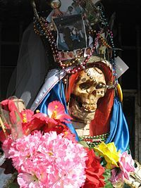 Santa-muerte-nlaredo2.jpg        A wide variety of powers, including love, prosperity, good health, fortune, healing, safe passage, protection against witchcraft, against assaults, against gun violence, against violent death. Protection of jobs such as police officers, taxi drivers, bar owners, bicycle messengers; criminal professions including smugglers and drug dealers; homosexuals and transgender people, prostitutes, people in poverty, and other categories of outcasts.