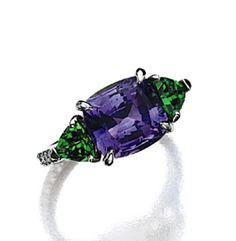 VIOLET SAPPHIRE AND TSAVORITE GARNET RING, PAOLO COSTAGLI.  The cushion-shaped sapphire weighing 4.96 carats, flanked by 2 triangular-shaped garnets weighing approximately 1.10 carats, the band decorated with small round diamonds weighing approximately .25 carat, mounted in platinum, size 6, maker's mark PC for Paolo Costagli. Fine Jewelry, Unique Jewelry, Jewelry Rings, Expensive Jewelry, Garnet Rings, Gems And Minerals, Green And Purple, Beautiful Rings, Ring Designs