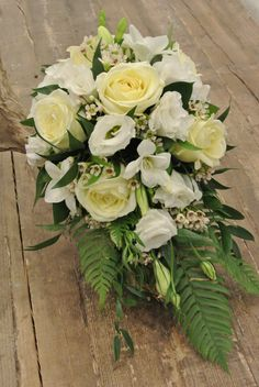 White trailing bridal bouquet with roses, lisianthus, freesias, wax flowers Italian ruscus and ferns. Designed by Forget-Me-Not Flowers in Banff.