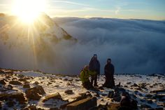"""Darren , Matt & Alison on the shoulder of Stob Coire An Lochan, Glencoe at about 5pm on Tuesday 10th February 2015. We had just completed a very successful Learning to Lead Winter Climbing Course. This was one of those """"magic moments"""", we had been in cloud for the entire duration of the climb so it was to climb out of it and see a few of the highest peaks sailing on a sea of cloud. Behind the group, the sun sets over Stob Coire Nam Beithe."""