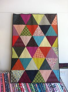 Triangle quilt with mostly solids and a few patterns in there