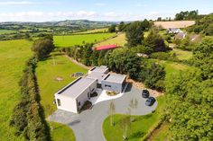 Birds eye aerial view of flat roofs of passive house with landscaped driveway and countryside in the distance.