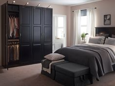 A large bedroom with a black bed and bedside tables. Shown together with a large black wardrobe combination and two footstools with gray cover.