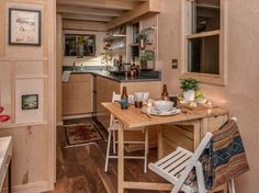 The dining room and kitchen of the Riverside tiny house; a 246 sq ft luxury home on wheels