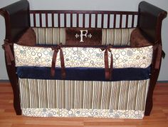 Foster Baby Bedding  This custom 3 pc baby crib bedding set includes a modern plush bumper pad, tailored crib skirt, and so soft minky edged and backed blanket.  The Brown, blue, green and cream stripe & coordinated geometric circles, chocolate grosgrain ties, and ultra soft chocolate minky combine softness and textured detail. Top quality and a modern touch for your little angel's nursery.