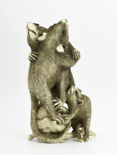 Netsuke of carved ivory, two rats fighting with a small rat beside them, unsigned: Japan