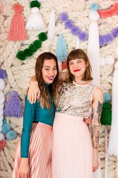 Create an Instagram-worthy backdrop for your upcoming holiday party, with this step-by-step tutorial for a DIY handknit backdrop, with colorful pom-poms and tassels, to upgrade any party decor. #ad