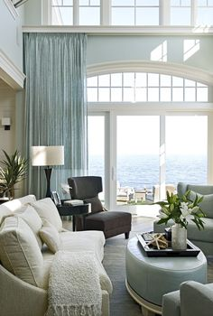 Eclectic Living Room with Double height living room, Transom window, Oval leather ottoman, Arched window, Cathedral ceiling