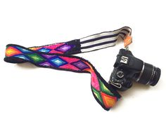 The Huipil Camera Strap is made with recycled embroidered fabric. With easy to use clasps and comfortable lining, this accessory is the perfect addition to your photo sessions. Each strap is made with second hand, used, unique and one-of-a-kind fabric. Color: Multi-Bright Pattern: Mixed One Size Metal Clasp Sturdy Construction Free Regular Shipping Each is Unique [...] Companies That Give Back, Camera Straps, People Around The World, Purses, Jewelry Accessories, Personalized Items, Gifts, Preserve, Coops