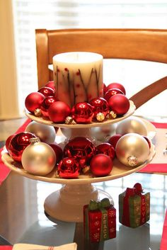 Christmas Centerpiece with stacked cake & dessert stands filled with a candle and some ornaments.