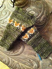 These are simple mittlets without thumbs or thumb openings. The figures are made with four-color stranded knitting but you can use only two (orange and green) and embroider white and black details afterwards. The widest circumference of the mittlet is 18 cm. The figure part is 7.5 cm and ribbing is 8 cm.
