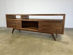 A mid century modern inspired console. Great for a TV, record player, books and anything else you would like to display. With 2 sliding doors which can give many different configurations. Hand applied oil / poly satin finish. Constructed out high quality walnut hardwood And veneer on a pro core plywood. ( My reason for using some veneers instead of all solid wood is it is more eco friendly and there less prone to warping than solid wood. I build each unit the way I would build it for myself…