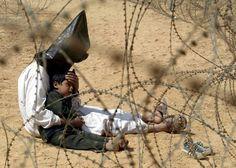 Un iracheno cerca di rassicurare suo figlio di quattro anni in un centro di raggruppamento di prigionieri di guerra vicino a Najaf, circa 160 chilometri a sud di Baghdad, in Iraq, 31 marzo 2003. (AP Photo/Jean-Marc Bouju