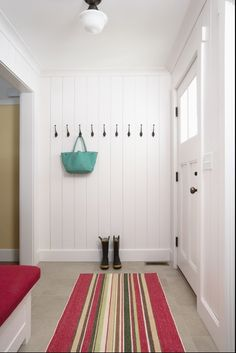 I kinda like the floor to ceiling white paneling. Simple. Perfect back door/mudroom entrance.