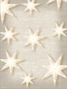 Paper stars on a white brick backdground. A great choice for holiday and Christmas themed photos.