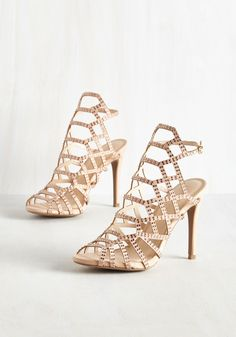 As the room parts in admiration of these vegan faux-suede pumps, you flash a sweet smile at the crowd. Commanding the room with their shimmering rose gold rhinestones, geometric cutout-adorned silhouette, and flirty peep toes, these darling beige heels are an illustration of supreme elegance.
